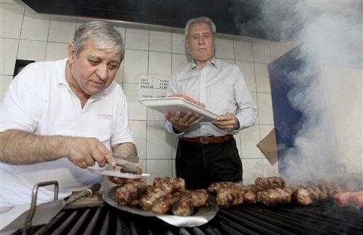 Sandu Andrei grilling meatballs with Ion Oita, The meatball King