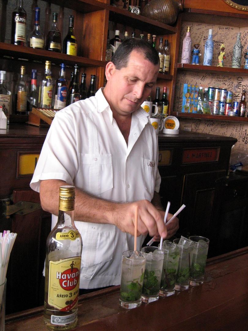 A bartender preparing mojitos