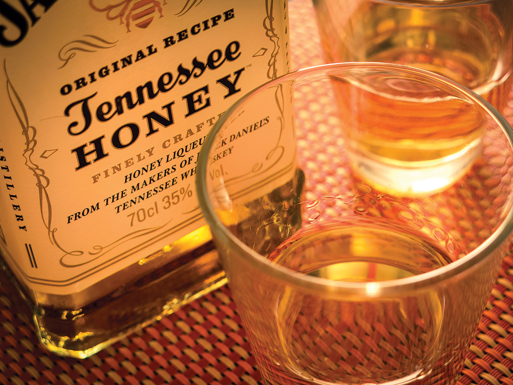 Milan, Italy - November 28th 2014: close up on a Jack Daniel's honey tennessee whisky bottle, with two glasses.