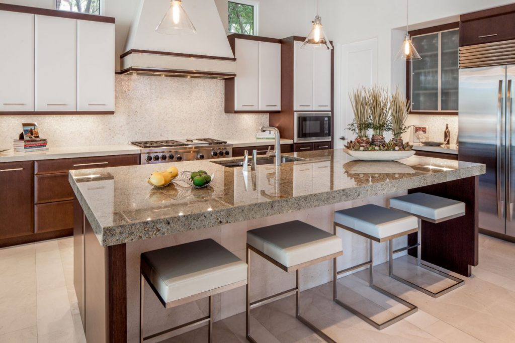 The streamlined kitchen is a study in practicality, featuring contrasting cabinets, a capiz shell backsplash, and stools that hide under the large island.