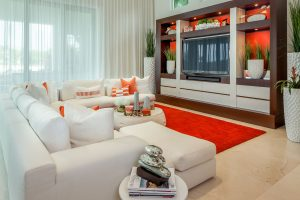The great room features an exciting balance of white furniture and orange statement pieces and accents
