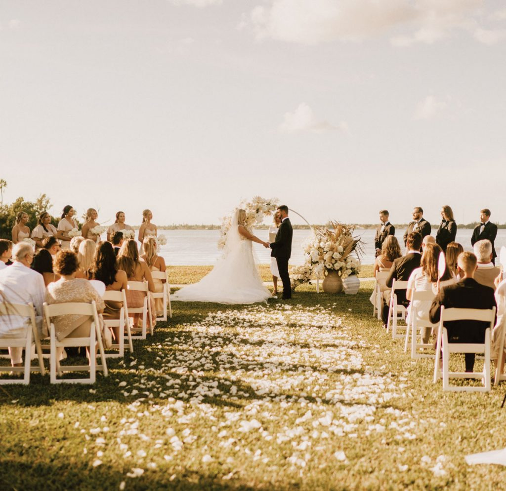 Le couple s'est marié devant un cerceau drapé de fleurs. Script Me Pretty a créé la signalisation, et Niche Event Rentals et Plithos Rentals ont fourni les locations.