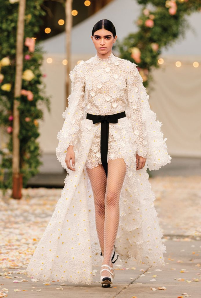 Haute Couture short guipure lace dress with hand-embossed daisies, an attached cape, and a black grosgrain belt (price upon request), Chanel